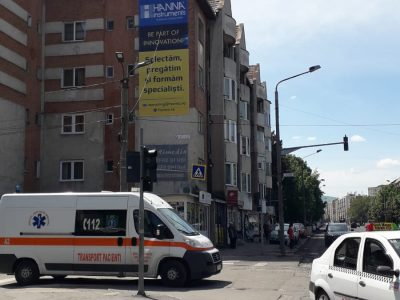 Panou publicitar de tip mesh amplasat pe clădire în oraș