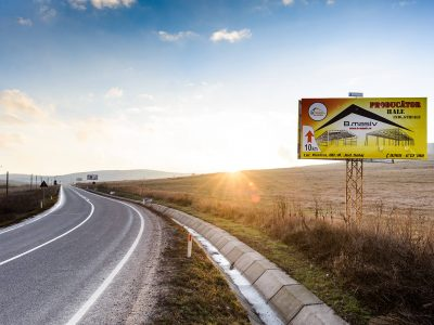 Panou publicitar tip unisign amplasat pe marginea drumului în timpul zilei